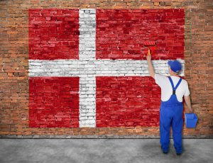 House painter paints flag of Denmark on old brick wall